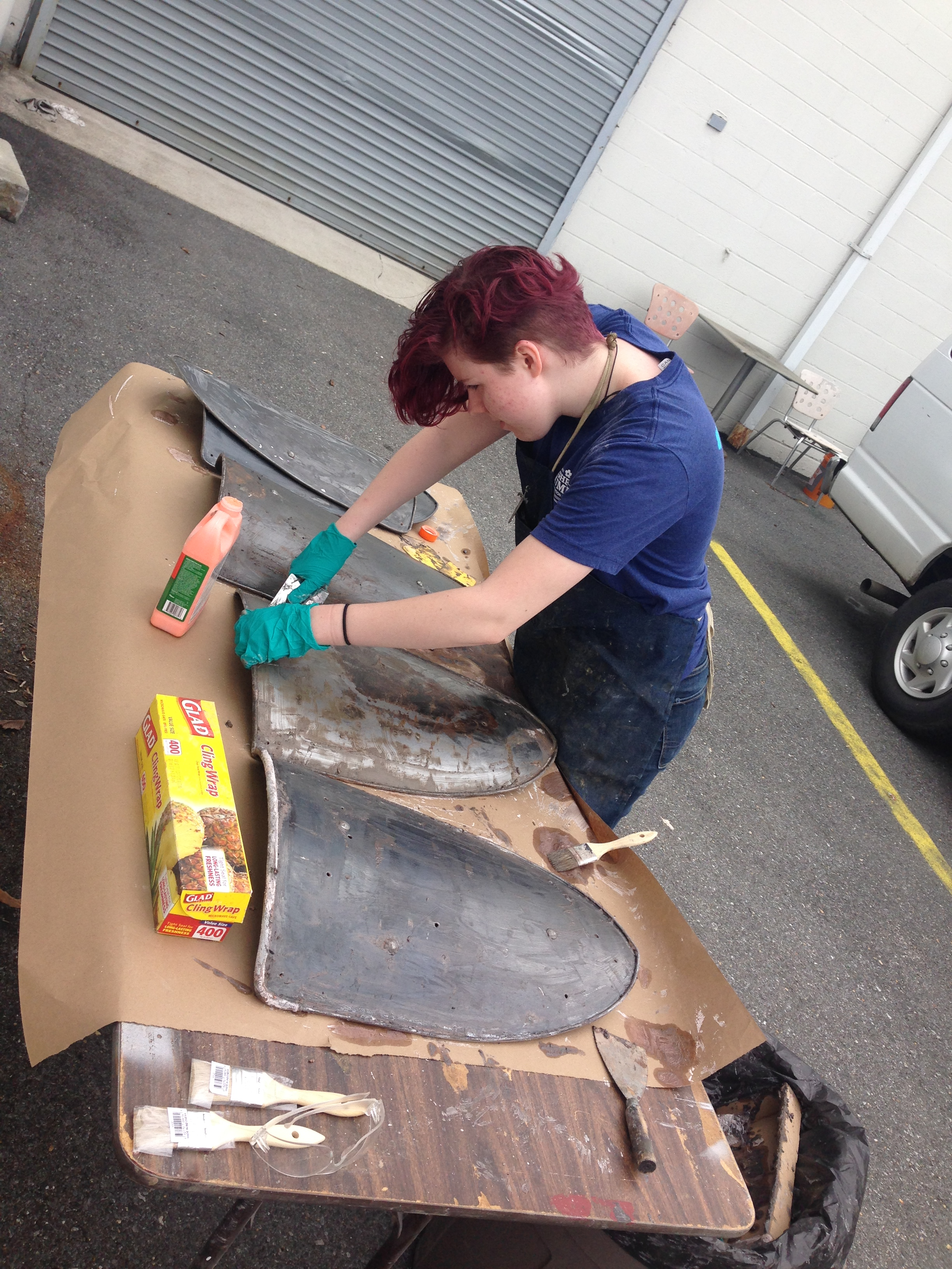Props intern Jesse Goodwin strips off paint – heraldry from a previous show.
