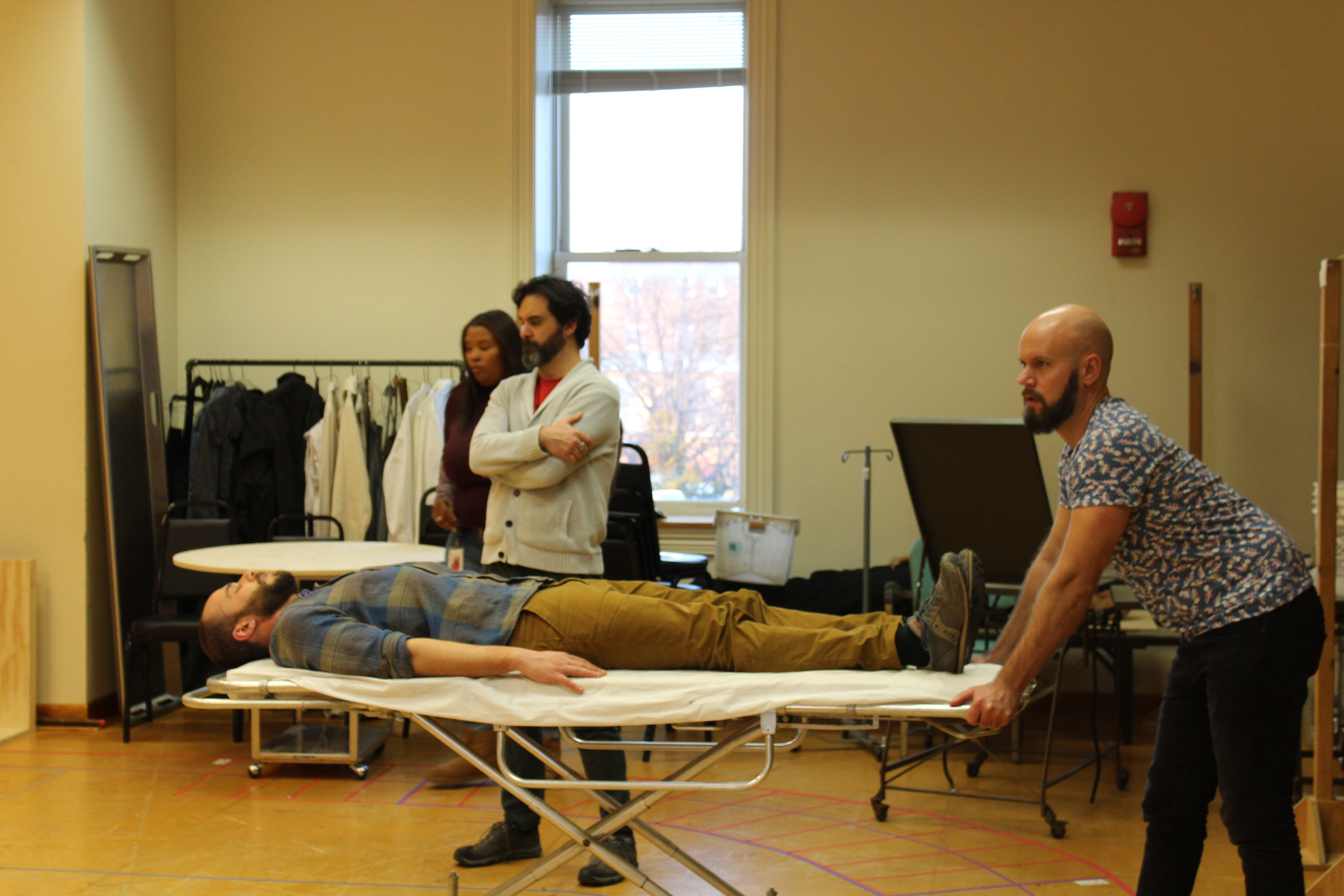Photo of Jonathan Feuer as Lord Gray (lying down), Production Assistant Chevonne Baylor, Cody Nickell as George, Duke of Clarence and Assistant Director Craig Baldwin in rehearsal.